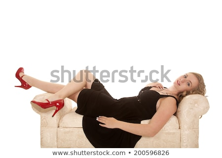 blonde girl in a black dress laying on a couch stock photo © carlodapino