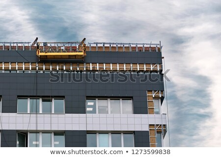 Workers hanging on the crane and repairing wall paneling on heat Stock photo © smuki