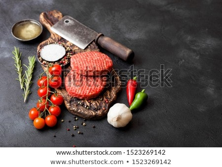 Fresh raw minced and grilled pepper beef burgers on vintage chopping board with buns onion and tomat Stock photo © DenisMArt