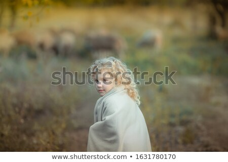 A blond curly haired girl covered with a blanket walks in a dark garden Stock photo © ElenaBatkova