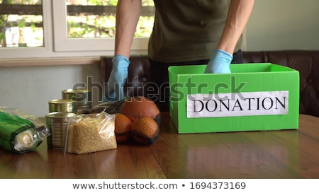 Volunteer in the protective medical mask and gloves putting food In donation box. Stock photo © Illia