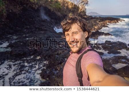 Smiling guy in the sea spray on the rocks Stock photo © galitskaya