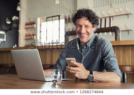 Image of smiling businessman using cellphone and earphones Stock photo © deandrobot