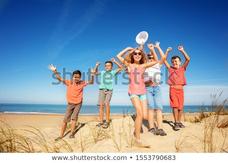 boy jumps on sand with  lifted hands Stock photo © Paha_L