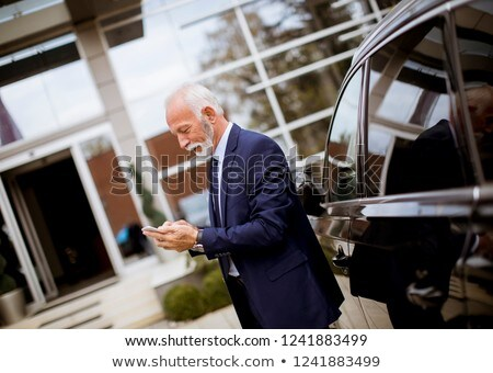 senior businessman using mobile phone near car stock photo © boggy