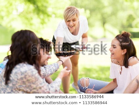 happy friends sharing pie at picnic in summer park Stock photo © dolgachov