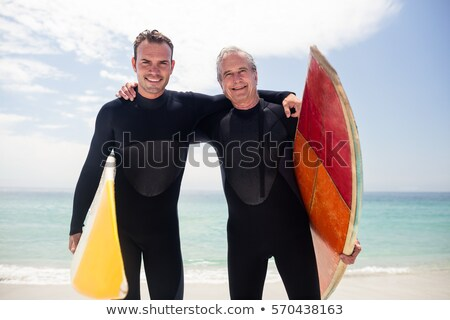 Front view of happy senior male surfer standing with surfboard and looking at camera on the beach  Stock photo © wavebreak_media