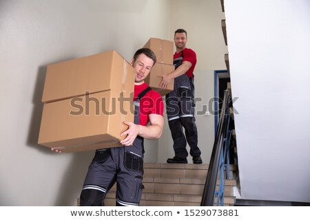 two male movers walking downward with boxes on staircase stock photo © andreypopov