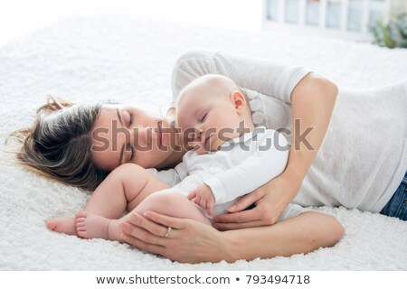 parents cuddling newborn baby in bed at home stock photo © lopolo