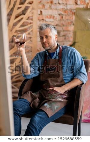 Töprengő művész üveg vörösbor néz festmény Stock fotó © pressmaster