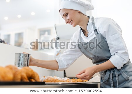 Confectioner woman powdering cocoa on sweet bread Stock photo © Kzenon