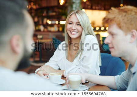 Happy blonde girl with toothy smile having cup of cappuccino with two guys Stock photo © pressmaster