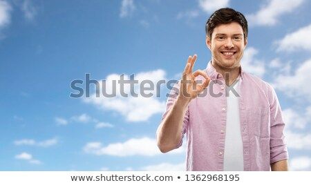 smiling young man showing ok hand sign over sky Stock photo © dolgachov