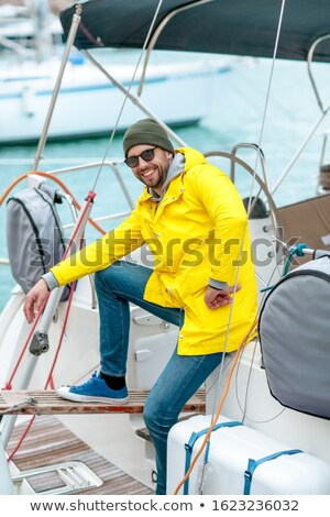 The owner of the sea vessel the captain of the boat smiles in the Bay near his ship Stock photo © ElenaBatkova
