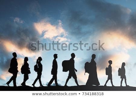 Emberek csomagok sétál csetepaté sziluett naplemente Stock fotó © AndreyPopov