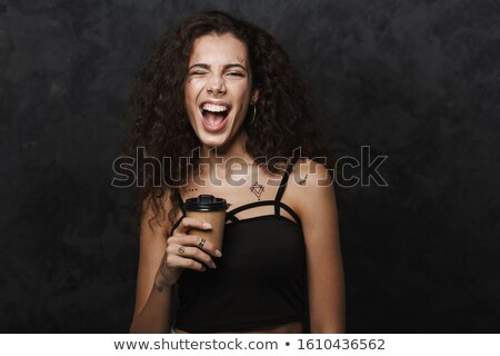 Image of nice cheerful woman winking and drinking coffee takeaway Stock photo © deandrobot