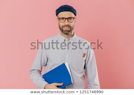 Image of self confident young male with stubble, wears transparent glasses, holds textbook under arm Stock photo © vkstudio