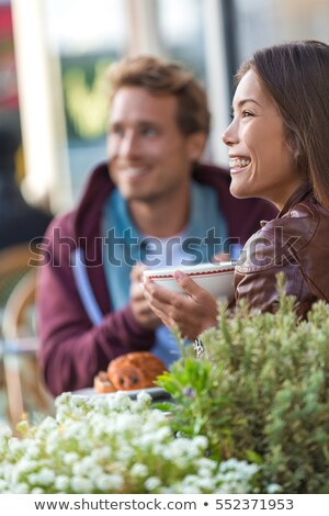 Happy people eating brunch at cafe. Young couple hipsters drinking coffee at restaurant table outsid Stock photo © Maridav