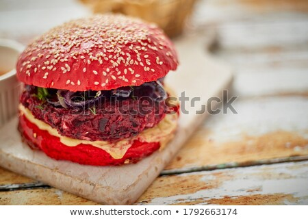 Homemade vegetable beetroot burgers. Red colored sesame bun. Served with goat cheese, feta Stock photo © dash