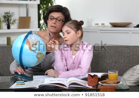 woman helping her granddaughter complete her geography homework stock photo © photography33