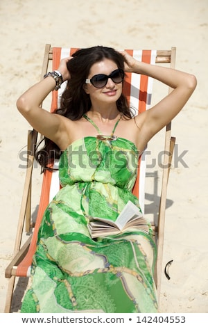 Young beautiful woman relaxing lying on a sun lounger Stock photo © Andersonrise