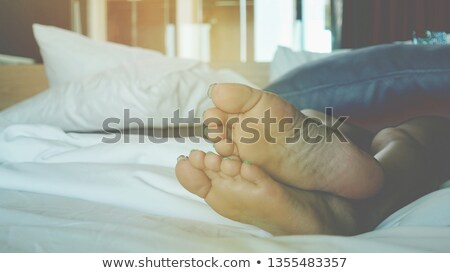 A woman sleeping under the duvet whit the legs uncovered. Stock photo © Lighthunter