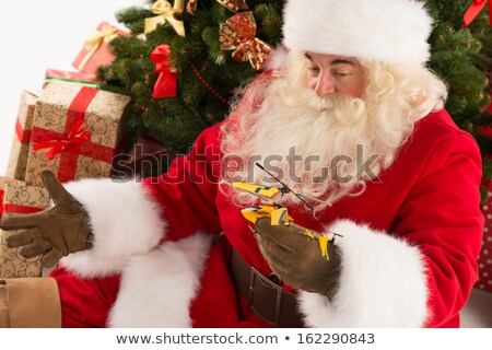 portrait of happy santa claus holding gift helicopter toy stock photo © hasloo