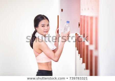Stock photo: Woman putting water bottle in locker