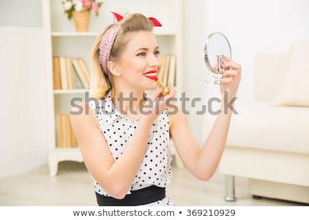 beautiful woman putting on lipstick stock photo © dash