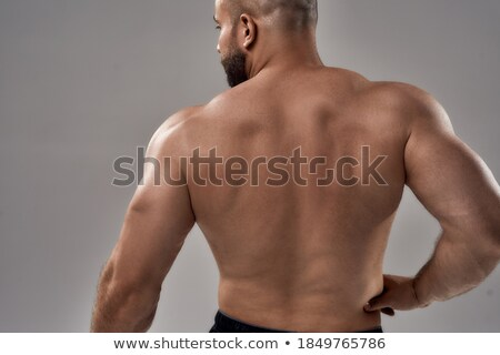 Rear view of a muscular man over gray background Stock photo © deandrobot