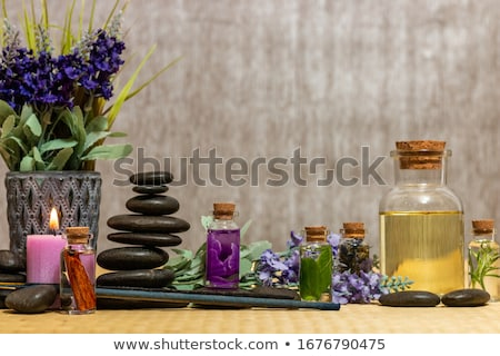 black spa stones, bottle with essence oil and chamomile flowers  Stock photo © tetkoren