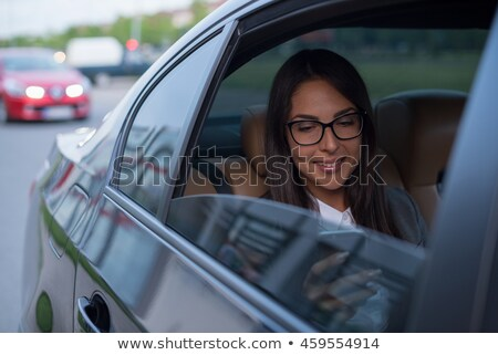 Woman riding in a car with chauffeur stock photo © deandrobot