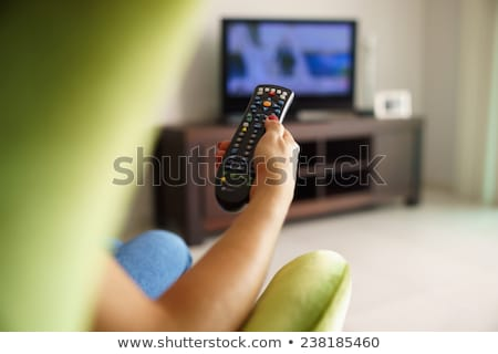 Young woman sitting on sofa holding tv remote and surfing progra Stock photo © manaemedia