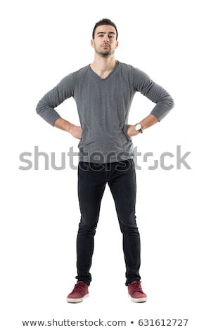 Serious suspicious young man standing with hands on hips Stock photo © deandrobot