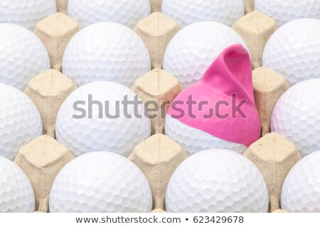 White golf balls in the box for eggs. Golf ball with funny cap. Stock photo © CaptureLight