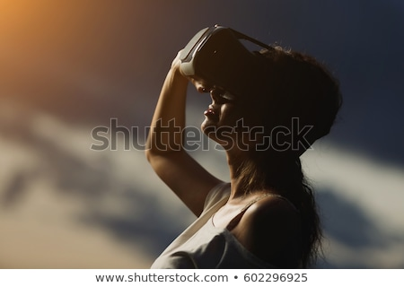 Beautiful young woman wearing virtual reality device Stock photo © deandrobot