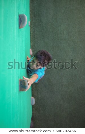 Boy reaching at climbing holds on green wall Stock photo © wavebreak_media