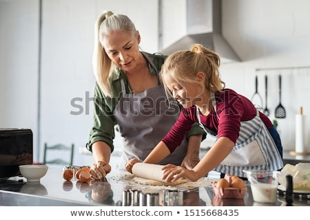 Grandmother helping granddaughter to flatten dough Stock photo © wavebreak_media