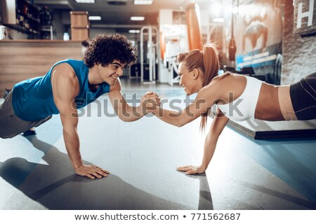 Fit smiling couple planking together in gym Stock photo © wavebreak_media