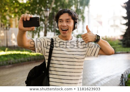 Excited casual man carrying backpack at the city street Stock photo © deandrobot