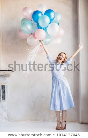 Blonde happy woman in light dress with stay in front of light wall stock photo © ruslanshramko