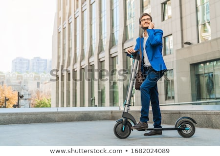 handsome young business man walking outdoors on scooter talking by mobile phone stock photo © deandrobot