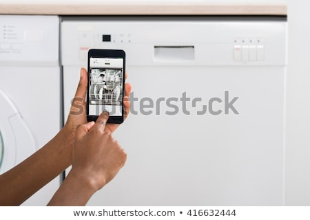 Stok fotoğraf: Woman Operating Dishwasher With Mobile Phone
