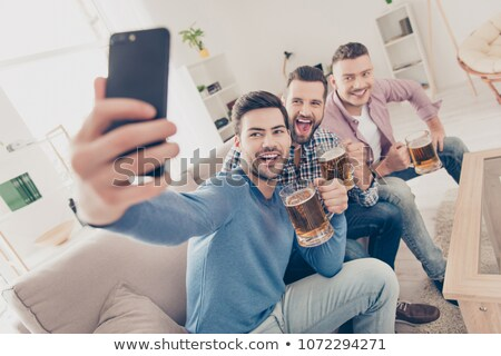 man drinking alcohol and calling on smartphone Stock photo © dolgachov