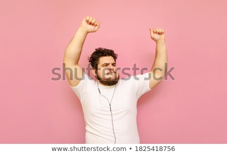 pleased bearded man in shirt and headphones listening music stock photo © deandrobot