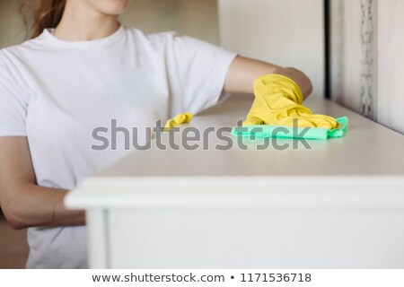 Crop of girl wearing in yellow protective rubber gloves, wiping furniture. stock photo © studiolucky