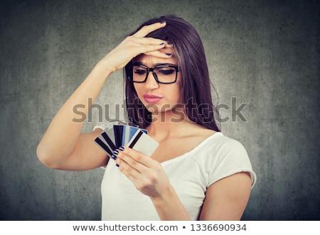 Mulher olhando muitos cartões de crédito completo Foto stock © ichiosea