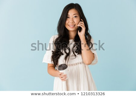 Asian beautiful woman isolated over blue background holding coffee talking by phone. Stock photo © deandrobot