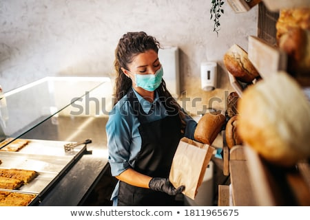 The young female baker working in kitchen  Stock photo © Elnur