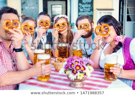 Group in Bavarian beer garden looking through pretzel holes Stock photo © Kzenon